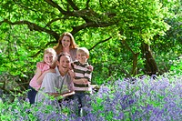 Family posing in field of bluebell flowers