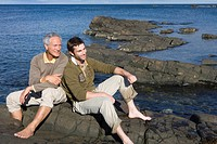 Two men relaxing on rock by sea