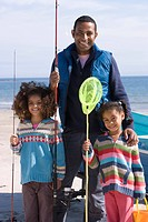 Portrait of father with daughters holding fishing nets on beach