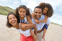Parents piggybacking daughters on beach