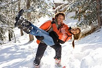 Mixed race couple playing in snow, man holding woman