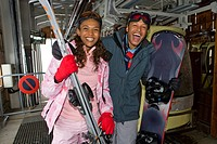 Mixed race couple on ski lift with skis and snowboard
