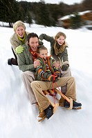 Young family sledding down snow slope