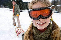 Young girl in snow goggles with father pulling sled in background