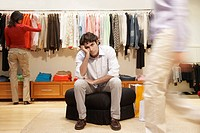 Bored young man in women´s clothing store
