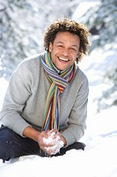 Portrait of mature man holding snowball in snow