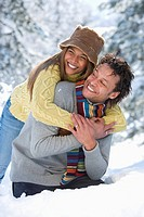 Portrait of mixed race couple hugging in snow
