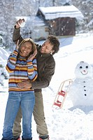 Mixed race couple playing in snow with snowball