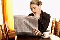 Mid adult woman reading newspaper in cafe