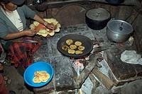 Woman baking pancakes, with cornmeal, Ecuadorian Andes, Casarpamba, province Imbabura, Ecuador, fireplace
