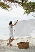 Woman Hanging Blanket on Clothesline