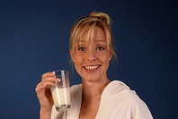 Young woman drinks a glass of milk
