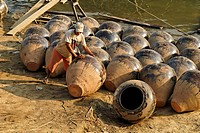 Man on the banks of Irrawaddy river with Martarban pots, Kyauk Myaung, Myanmar