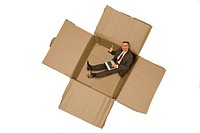 Businessman sitting his his new office made from paperboard