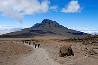 Group of mountaineers and local porters on Marangu Route in front of the summit of Mawenzi Kilimanjaro Tanzania