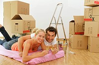 Happy couple surrounded by cardboard boxes celebrating their move with champagne