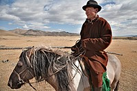 Mongolian horseman sports a stylish felt hat and carries his uurga, north central Mongolia The uurga is a long pole with loop of rope on the far end u...