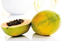 Papayas (Carica papaya), whole and halved