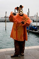 Golden harlequin court jester costume and mask in front of gondolas, Carnevale di Venezia, Carneval in Venice, Italy