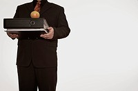 Businessman holding files and an apple