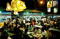 People enjoying seafood prepared by food stalls in outdoor seafood market in Zhoushan, Shanghai, China
