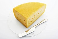 Cheese wedge on glass cutting board with silver cheese knife