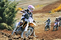 Female motocross racer rounding corner with other racers in pursuit, Nanaimo Wastelands, Nanaimo, Vancouver Island, British Columbia, Canada