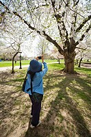 Woman, with two shoulder bags, taking pictures in a city park