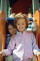 Two little girls sitting together on slide, portrait