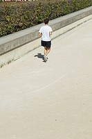Man jogging in park, rear view
