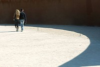 Couple walking on sunlit gravel, rear view