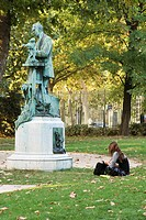 France, Paris, female sitting on grass near statue in park