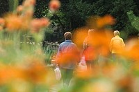 France, Paris, Buttes Chaumont, pedestrians walking in park, viewed through flowers