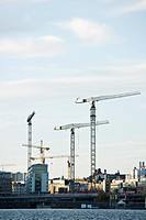 Sweden, Stockholm, construction cranes along water's edge