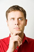 Man in a red shirt looking thoughtfully upwards