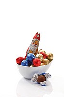 Small porcelain bowl with a chocolate Santa and chocolate balls in coloured wrapping