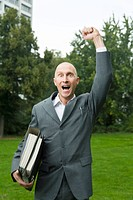 Businessman with files under his arm celebrating in the park with a clenched fist