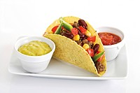 Taco shell with chili con carne, guacamole and tomato salsa