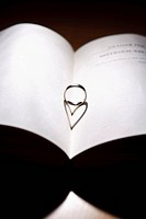 Ring with a heart-shaped shadow on an open book