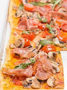Pizza topped with ham, tomatoes, mushrooms and rocket