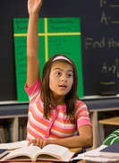 Hispanic girl with arm raised in classroom