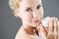 A middle_aged woman holding a pot of moisturising cream