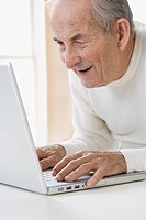 Senior Hispanic man typing on laptop