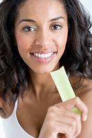 A woman holding a stick of celery
