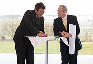 Two businessmen looking at blueprints in an office building