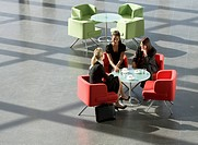 Three businesswomen having a meeting over a hot drink in an office building