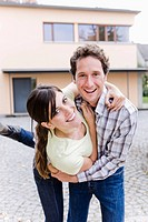 portrait of happy young couple in front of their new home
