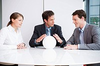 three business people sitting around table looking at crystal ball