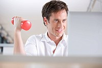 businessman exercising with dumb bell while sitting at laptop computer