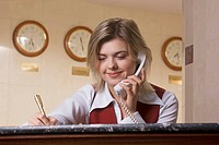 portrait of young hotel receptionist talking on telephone and taking down notes